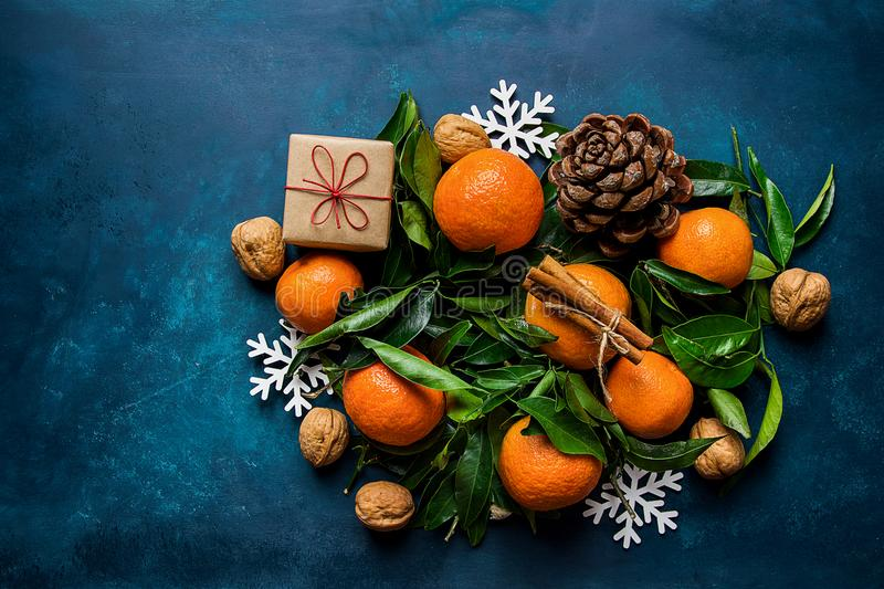 Bright Tangerines Green Leaves Pine Cones Gift Box Snow Flakes Ornaments on Dark Blue Background. Christmas royalty free stock photos