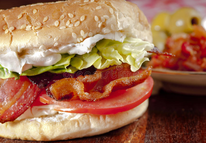 Bright, tasty and healthy BLT. Bacon, lettuce and tomato sandwich or BLT freshly made, with vibrant, healthy colours on a wood board with a ñlate of tomato stock image