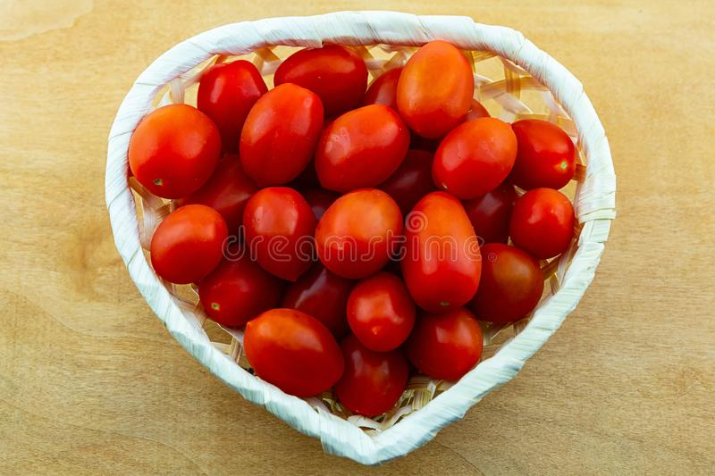 Bright tomatoes red juicy vegetables in a white basket heart shape close-up on a wooden background close-up stock image
