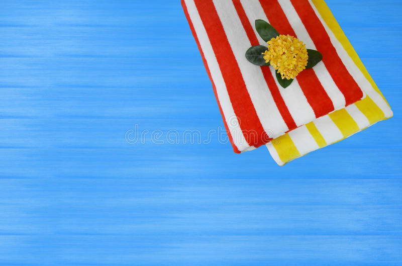 Bright towel striped red yellow white On a blue wooden floor for web design or graphic art image. Top view with copy space stock images