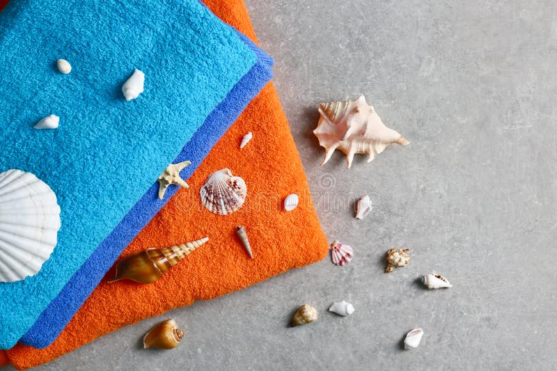 Bright towels and seashells on grey table stock photography