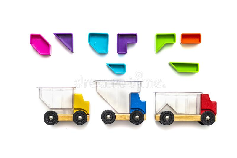 Bright toy cars with a transparent body. Multi-colored blocks - puzzles up above the cars. isolated white background. Concept royalty free stock photo