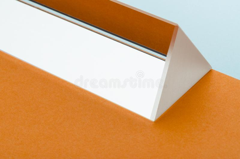 Bright triangular prism on orange-blue background. Minimalism, abstraction royalty free stock photo
