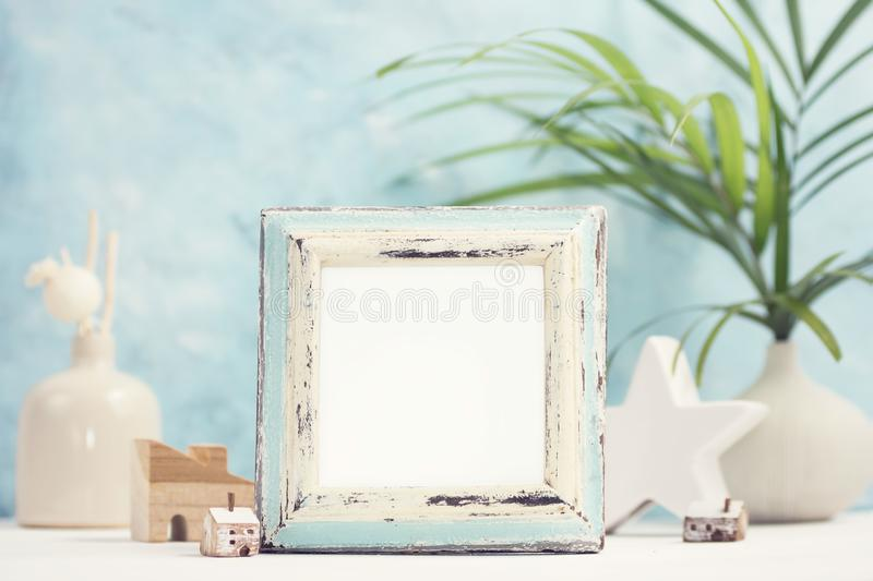 Bright tropical mock up with vintage white and blue photo frame, palm leaves in vase and home decor against blue wall royalty free stock photography