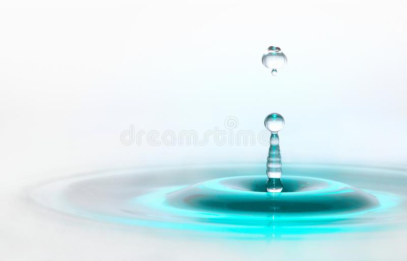 Bright turquoise blue waterdrop wallpaper. Nice waterdrop column formation, room for text. Sony DSLR, Tamron 90mm macro lense stock image