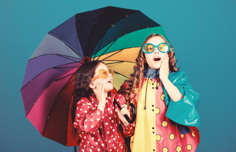 Bright umbrella. Happy childhood. It is easier to be happy together. Be rainbow in someones cloud. Rainy weather with. Proper garments. Walk under umbrella royalty free stock image