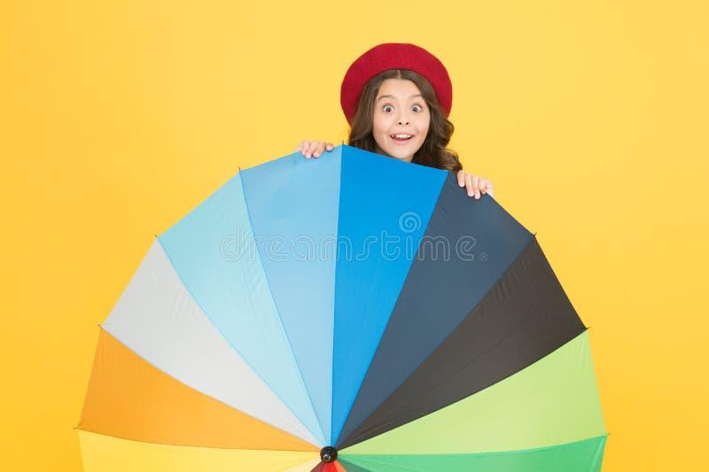Bright umbrella. Have fun. Kid girl happy behind colorful rainbow umbrella. Rainy weather with proper garments. Positivity concept. Rainy day fun. Hiding stock images
