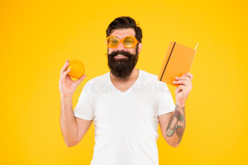 Bright and vibrant. Man bearded cheerful smiling hipster wear orange color sunglasses while hold orange fruit and book royalty free stock photos