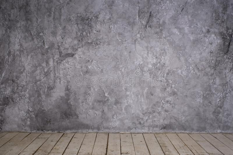 Bright vintage loft interior. With wooden floor, textured aged grey plaster concrete on the wall. Empty royalty free stock image