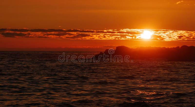 Bright, vivid sky at sunset over ocean stock image