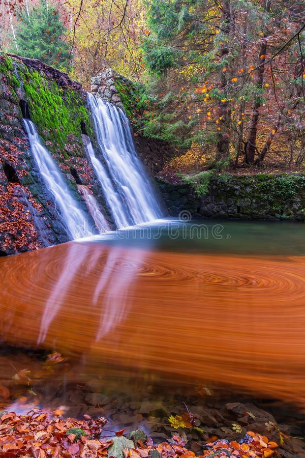 Bright waterfall fduring fall. It is colored by orarge colour from leaves stock photography
