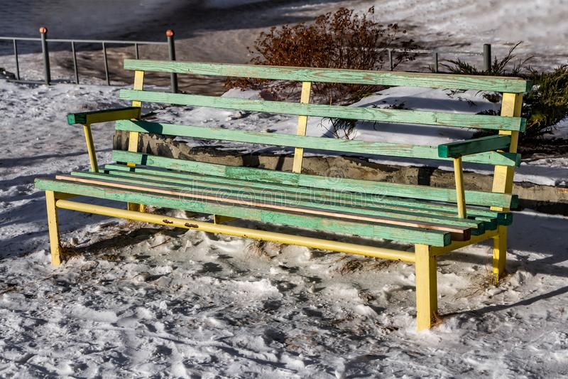 A bright wet wooden painted yellow and green color beautiful bench with yellow metal legs is on a white snow in the courtyard in. A bright wet wooden painted royalty free stock photos