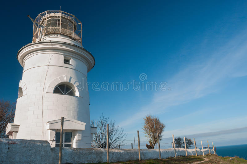 Bright white lighthouse on blue sky background royalty free stock photography