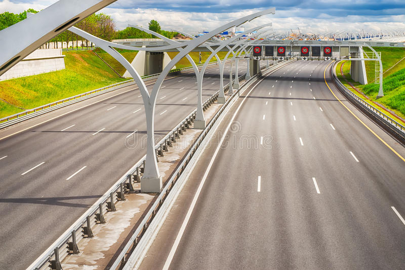 Bright wide high speed highway against distant industrial landsc royalty free stock photography