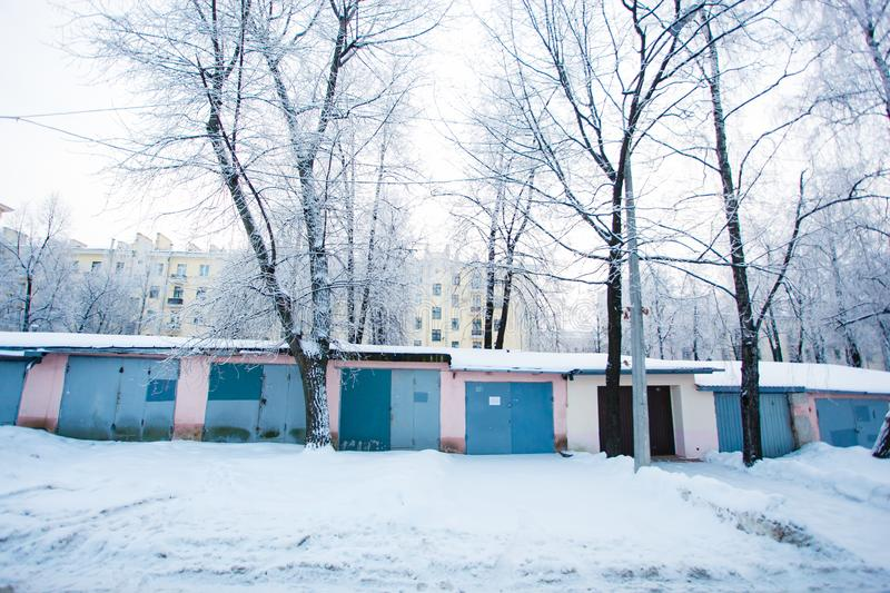 Winter morning. Chain of garages surrounded by snow piles. Bright winter morning. A chain of garages surrounded by snow piles stock photo