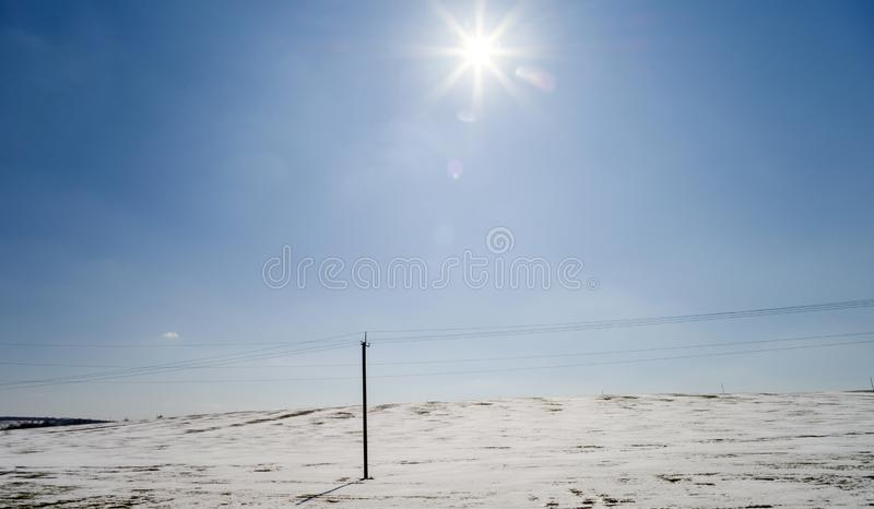 The bright winter sun shines over a frozen field on a hill with a power line stock photography