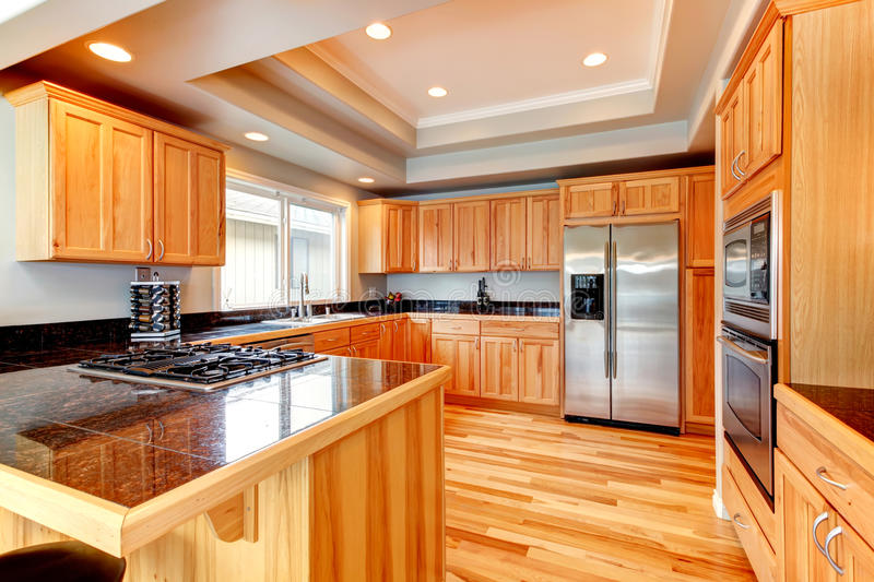 Bright wood kitchen with coffered ceiling. Llight tones wood kitchen with hardfloor and white coffered ceiling royalty free stock photo