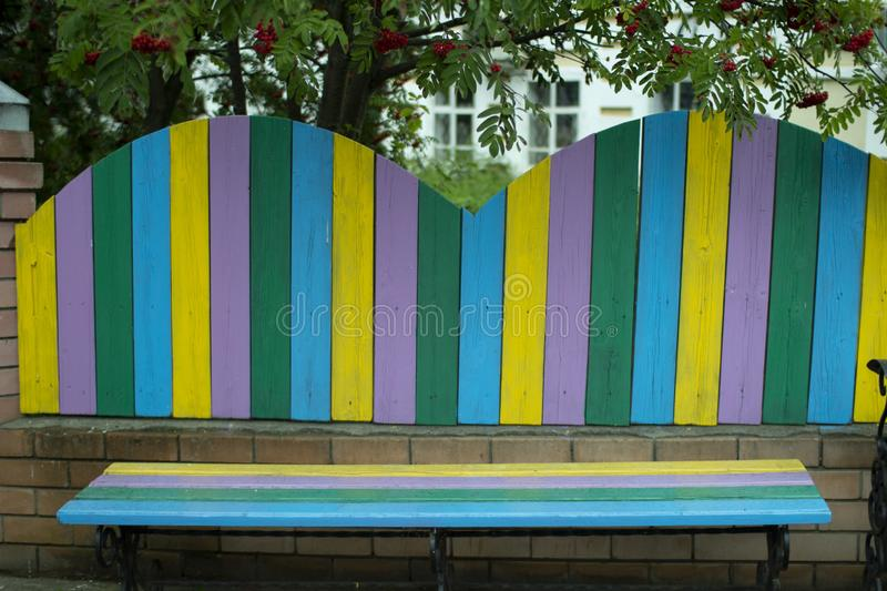 Bright wooden fence with each Board of different color stock images