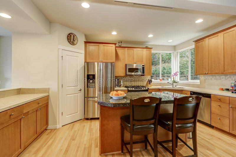 Bright wooden kitchen room with stainless steel appliances. Kitchen island with bar stools light tones hardwood floor. Northwest, USA stock image