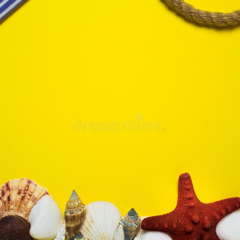 Bright yellow background in marine style with seashells, starfish and other marine attributes for cards, frames, visual advertisin. G in square frame stock images