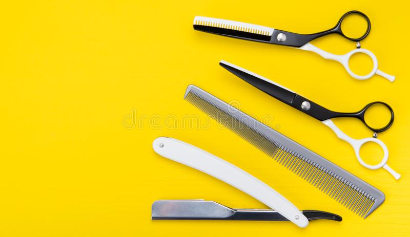 Bright yellow background. a set of items for cutting hair, scissors, and combs, and dangerous stock photography