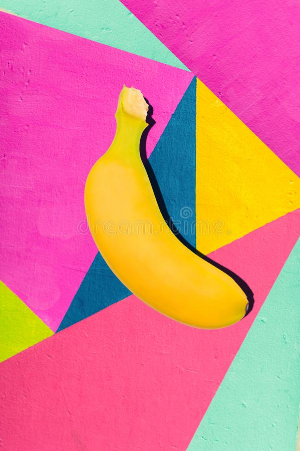 Bright yellow banana on geometric background of wall with bright tones. stock images