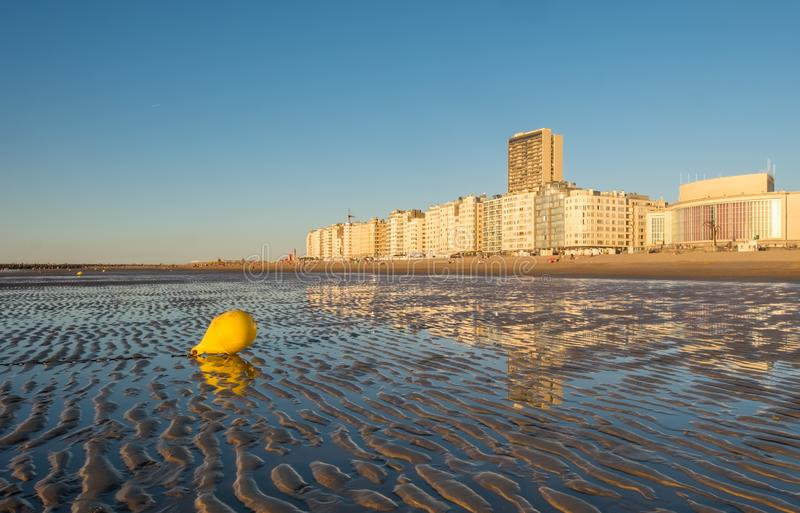 Bright yellow buoy on the beach of Ostend in Belgium. Bright yellow buoy on the beach of Oostende with city skyline in the background, Thursday 2 August 2018 stock photo