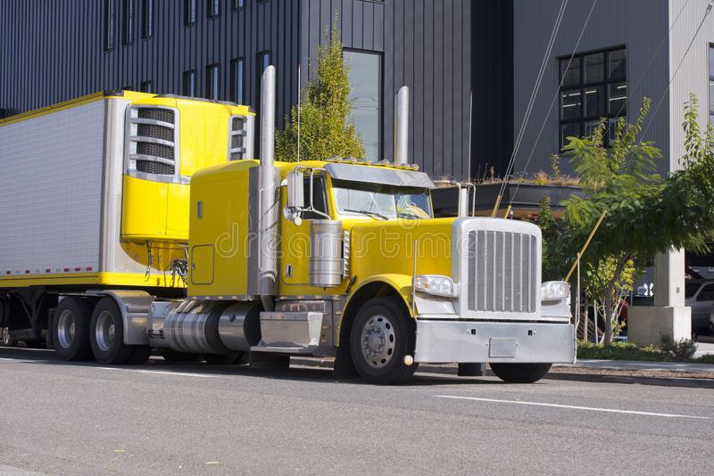 Bright yellow classic big rig semi truck with refrigeration unit. Bright yellow American classic big rig semi truck fleet with freezer semi trailer and tall royalty free stock images