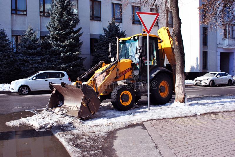 Bright yellow excavator tractor cleaning snow on the road along street, side view, snowy winter in Kharkiv stock photo