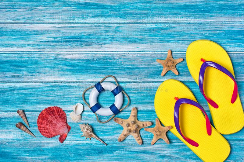 Bright yellow flip flops with seashells and starfish as concept of vacation time stock photo