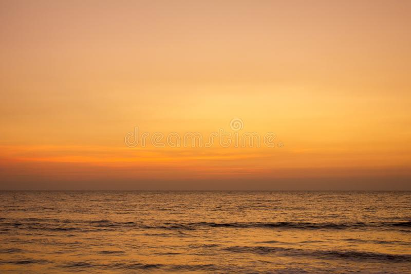 A bright yellow gray pink sunset sky over the ocean. Bright yellow gray pink sunset sky over the ocean stock photos
