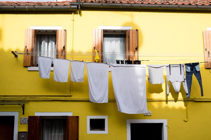 Bright yellow house with shutters and washing hanging out on the island of Burano, Venice. royalty free stock image