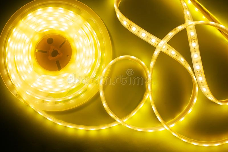 Bright yellow LED strip, diode strip, a coil  of silicone strip. Close-up royalty free stock photography