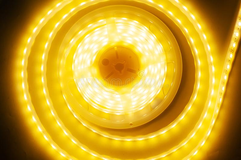 Bright yellow LED strip, diode strip, a coil  of silicone strip. Close-up royalty free stock images