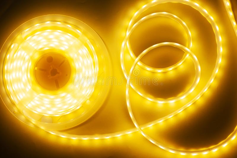 Bright yellow LED strip, diode strip, a coil  of silicone strip. Close-up royalty free stock photos