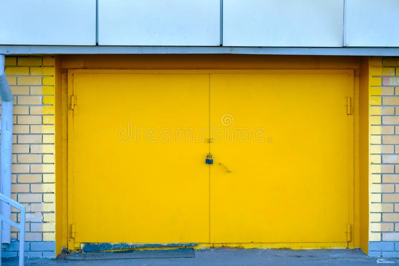 Bright yellow metal door from the garage locked. Onto a brick wall background stock photography