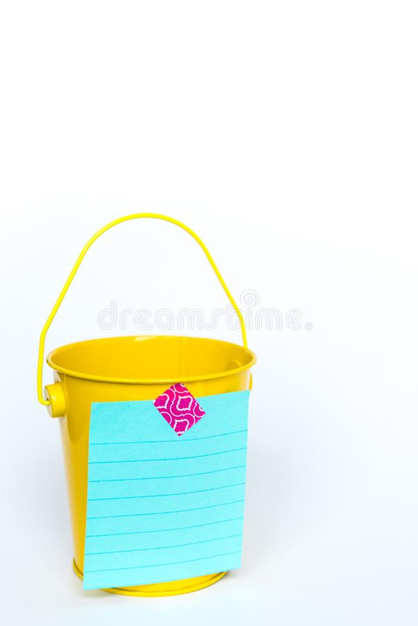 Bright yellow metal pail with aqua colored lined paper taped to front with pink washi tape on solid white background stock image