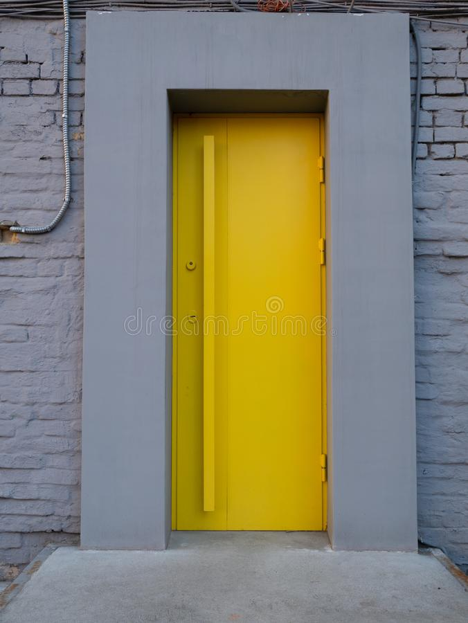 Bright yellow metallic door in grey wall. entrance to city cafe stock photos