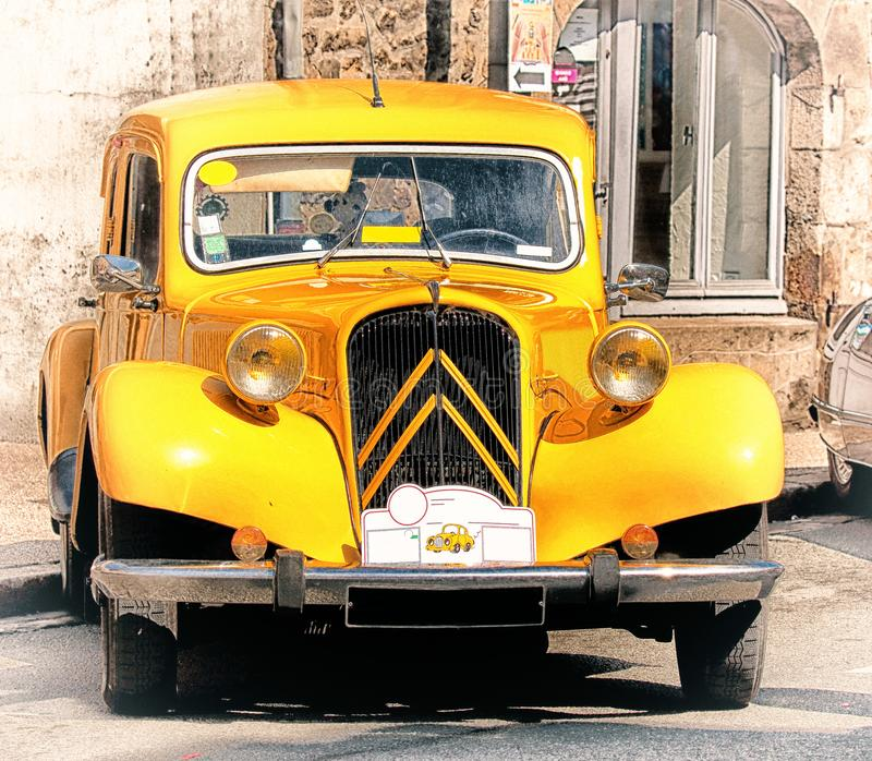 Bright yellow old vintage car in the main street in Ernée, Mayenne, France at the Foire st Gregoire 2018 stock photos