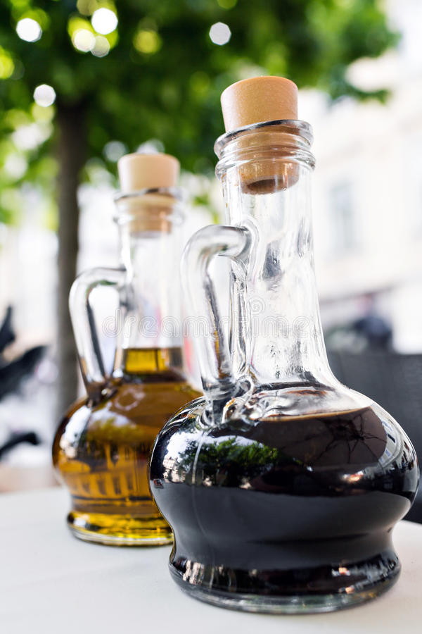 Bright yellow olive oil and black balsamic vinegar on the restaurant kitchen table. Two bottles foreground. Bottling of royalty free stock photo
