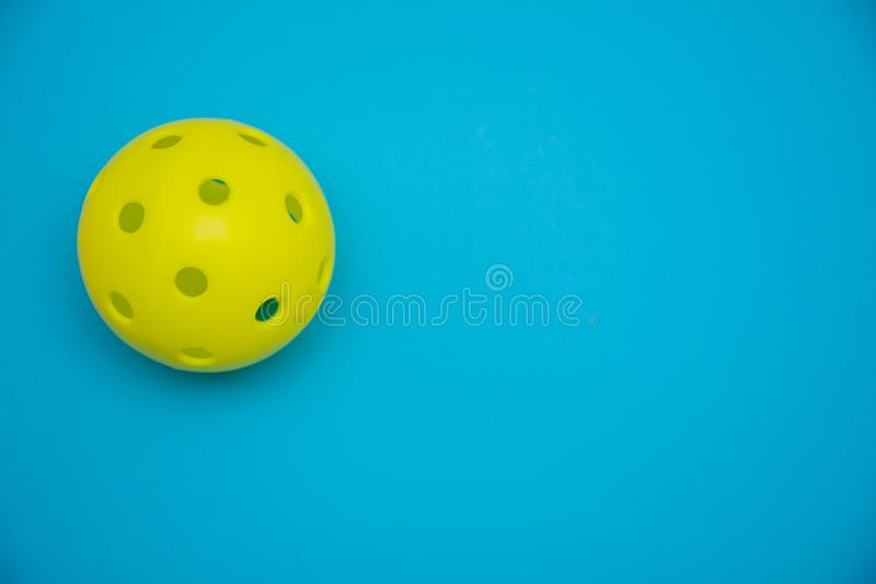 Bright yellow pickleball or whiffle ball on a solid bright blue flat lay background symbolizing sports and activity with copy stock image