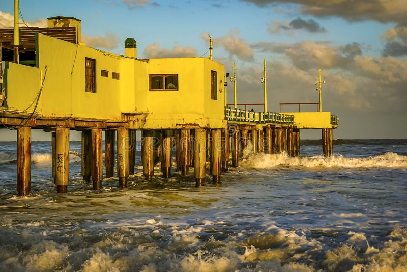 Pier in Pinamar Coast Argentina. Bright yellow pier building in Pinamar, Argentina at sunset with clouds stock photography