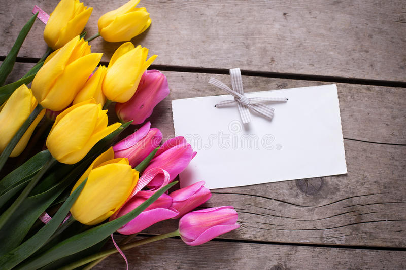 Bright yellow and pink spring tulips and empty tag on vintage w. Ooden background. Selective focus. Place for text stock images
