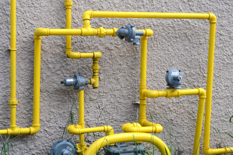 Yellow pipes mounted to a stucco wall. Bright yellow pipes and gauges mounted onto a stucco wall of a building. Winnipeg, Manitoba. Day. Summer stock photography