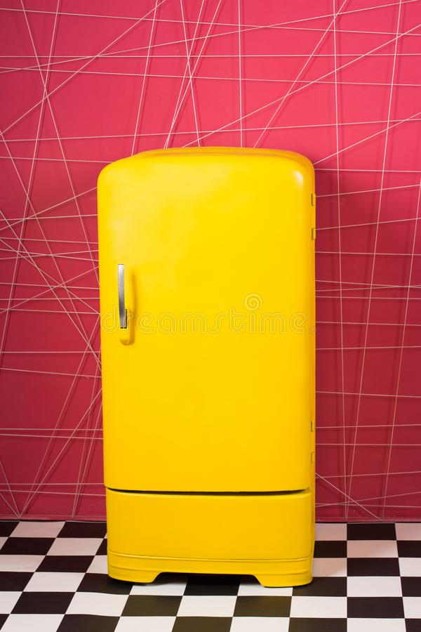 Bright yellow refrigerator in pink interior. Retro fridge looks awesome in modern interior. Stylish interior details royalty free stock photos