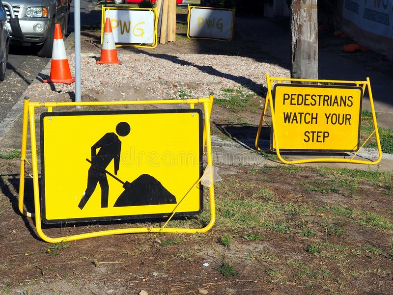 Roadwork Signs, Pedestrians Mind Your Step. Bright yellow safety warning signs of construction work, pedestrians mind your step because of broken pavement royalty free stock photography