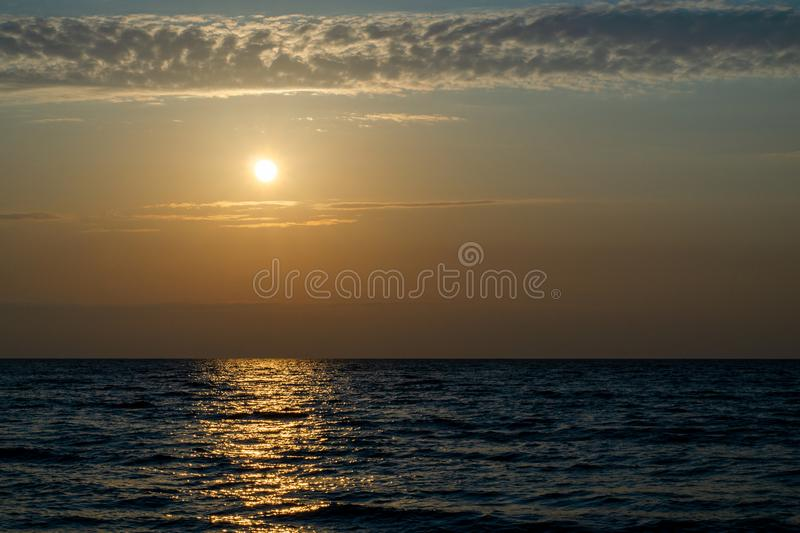 Bright yellow sun over the sea at dusk stock image
