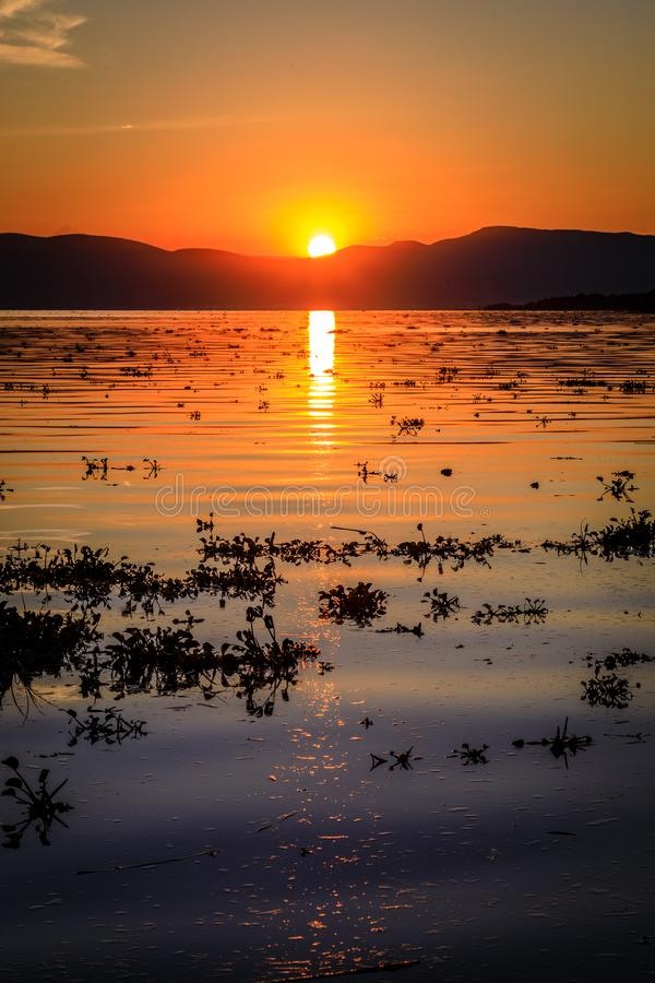 Bright yellow and vivid orange sunset reflecting on a rippled Lake Chapala in Ajijic Mexico. Bright yellow and orange sunset reflecting on a rippled Lake Chapala stock photography