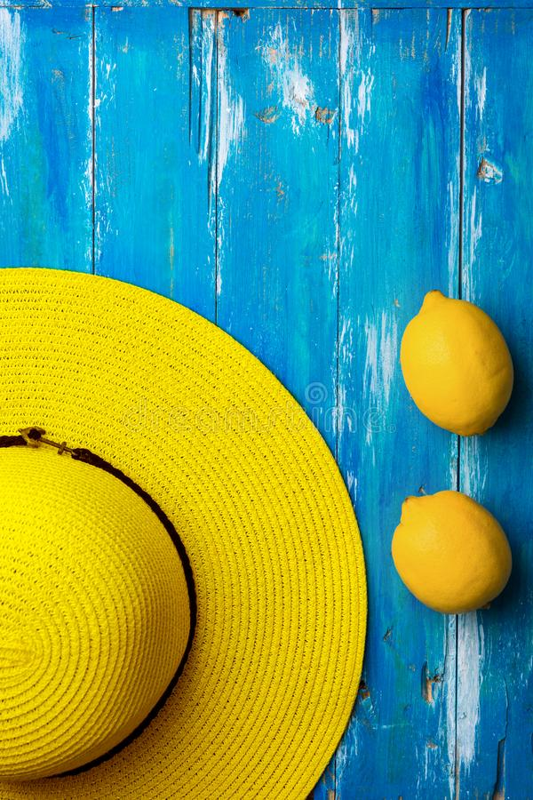 Bright yellow womens straw hat ripe organic lemons on old painted plank wood blue background. Summer vacation fun concept stock photo
