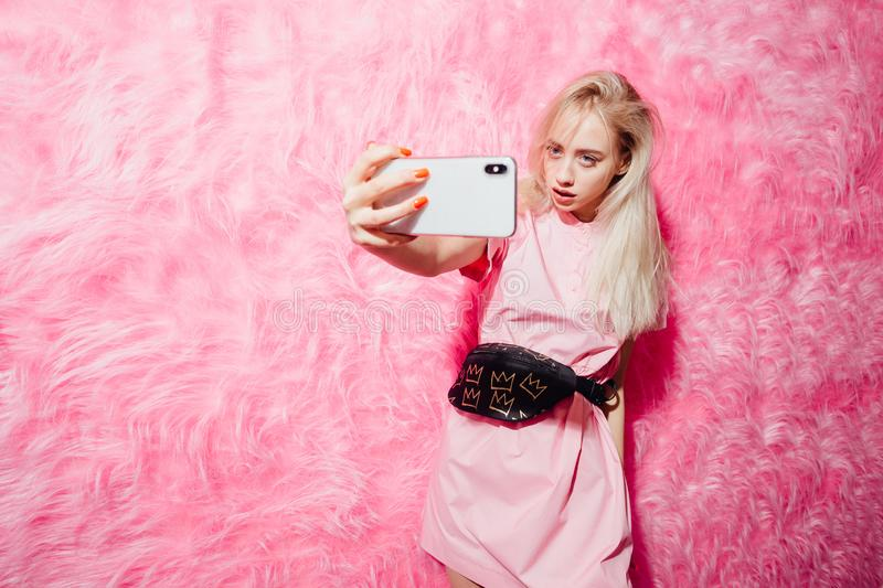 Bright young girl blogger dressed in fashion pink dress takes a selfie on her smartphone on the background of pink fur stock photo